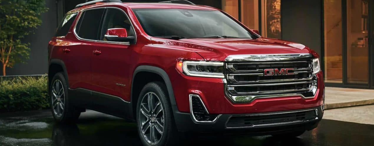 A red 2021 GMC Acadia is parked in a driveway after winning the 2021 GMC Acadia vs 2021 Ford Explorer comparison.