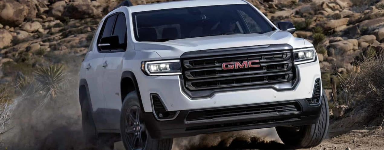 A white 2021 GMC Acadia AT4 is off-roading after winning the 2021 GMC Acadia vs 2021 Jeep Grand Cherokee comparison.