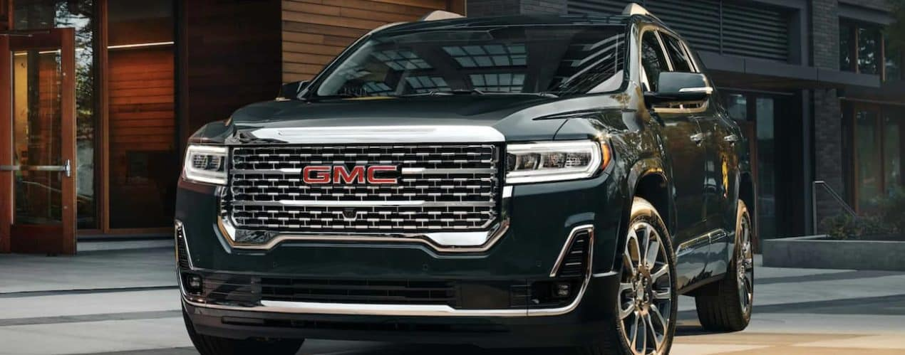 A black 2021 GMC Acadia is parked in a driveway of a modern house.