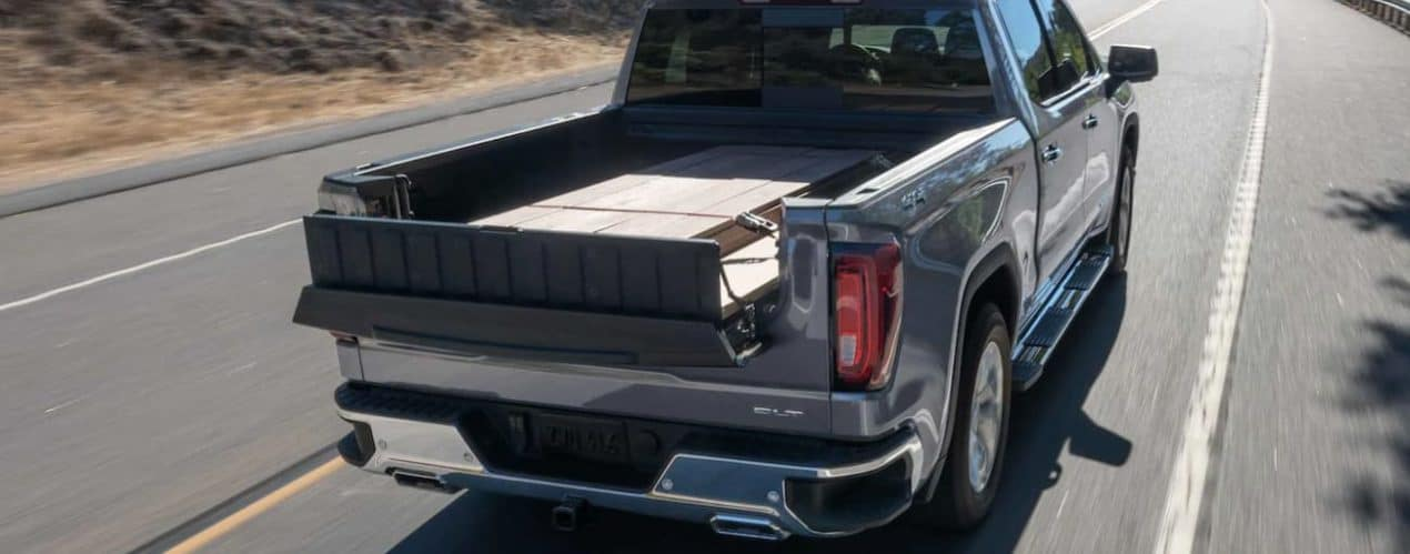 The MultiPro tailgate is shown in use on a grey 2021 GMC Sierra 1500 carrying wood.