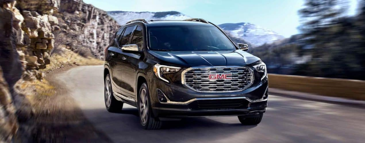 A black 2021 GMC Terrain is driving on a mountain road after winning the 2021 GMC Terrain vs 2021 GMC Terrain vs 2021 Jeep Compass comparison.