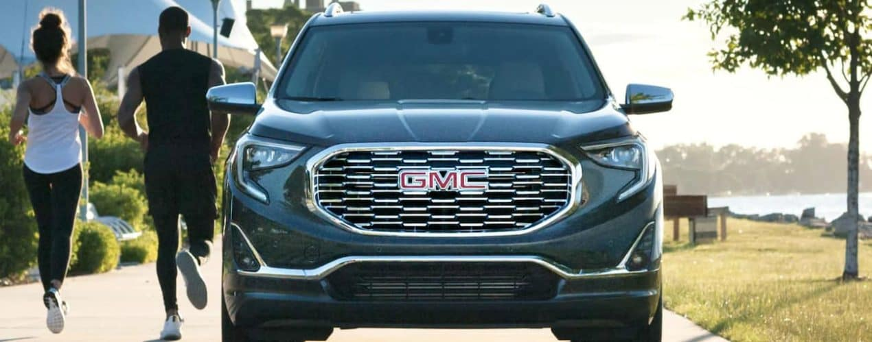 A couple is running past a grey 2021 GMC Terrain shown from the front in a park.