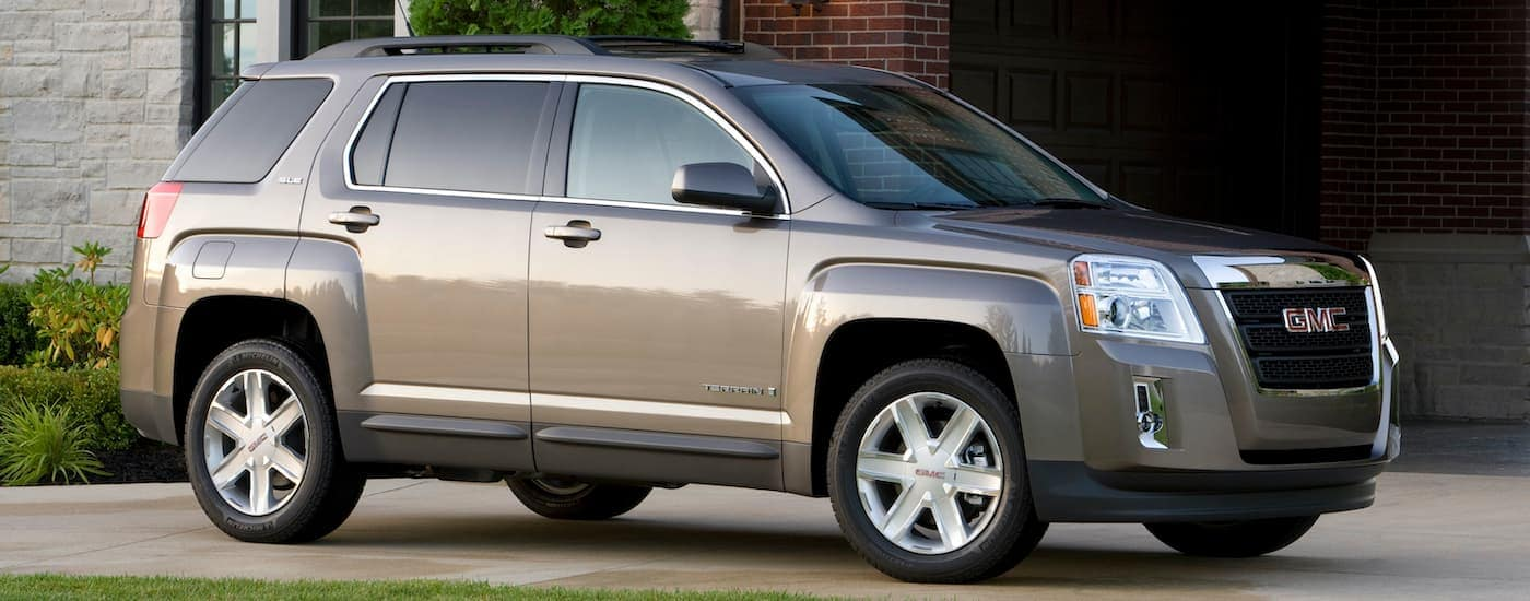 A tan 2010 GMC Terrain is shown from the side parked in front of a house.