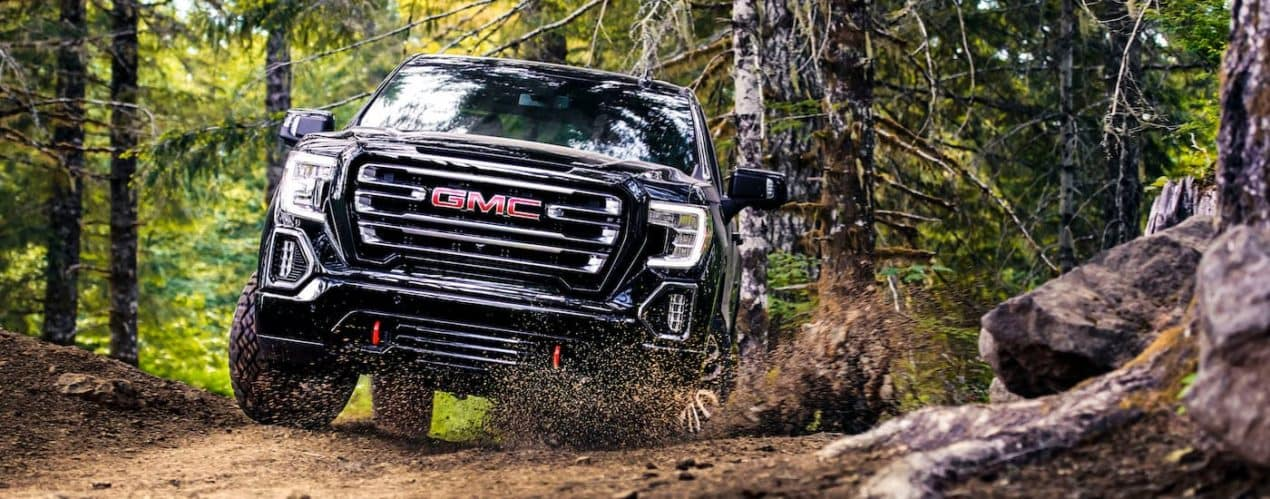 A black 2021 GMC Sierra 1500 AT4 is shown kicking up dirt while off-roading.