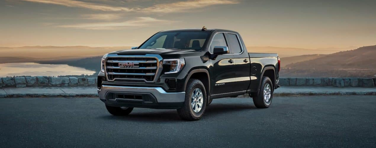 A black 2021 GMC Sierra 1500 is shown with a lake in the background after winning the 2021 GMC Sierra 1500 vs 2021 Toyota Tundra comparison.