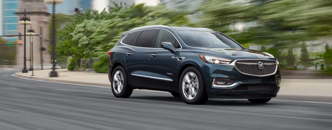 A dark blue 2021 Buick Enclave is shown exiting a corner after winning the competition of the 2021 Buick Enclave vs 2021 Honda Pilot.