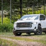 A white 2020 GMC Acadia AT4 is parked in the grass after leaving a used GMC SUV dealer.