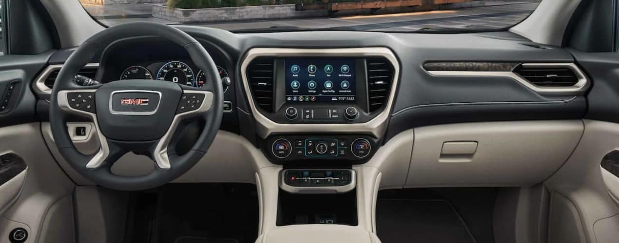 The interior of a 2021 GMC Acadia shows the steering wheel and infotainment screen.