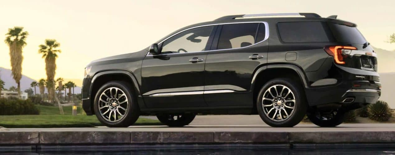 A black 2021 GMC Acadia is shown from the side parked in the desert.