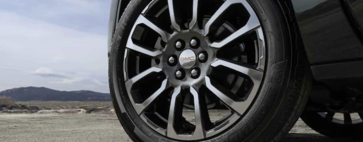 A black 20201 GMC Acadia shows a close up of a tire.