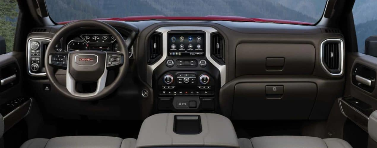 The interior of a 2021 GMC Sierra 2500 HD shows the steering wheel and infotainment screen.
