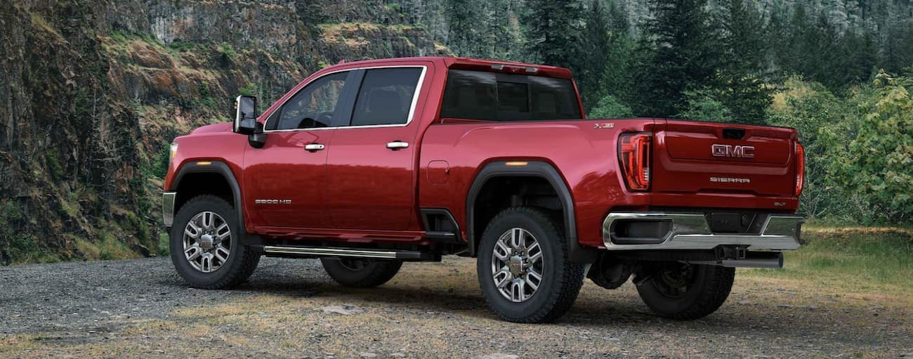 A red 2021 GMC Sierra 2500 is parked in the forest.