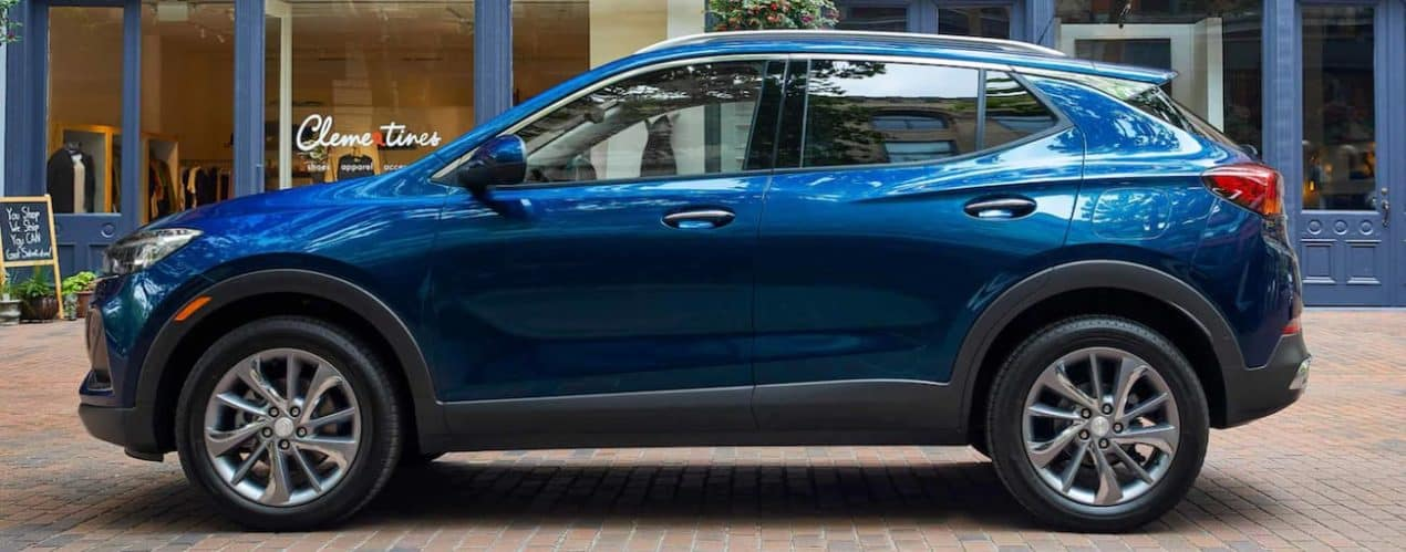 A blue 2022 Buick Encore GX is shown from the side parked in front of a modern building.