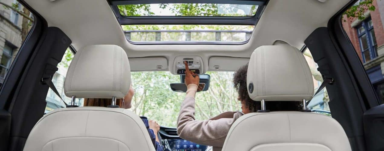 The white interior of a 2022 Buick Encore GX shows people sitting in the front seats.
