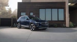 A blue 2022 Buick Envision is shown parked in front of a modern house.