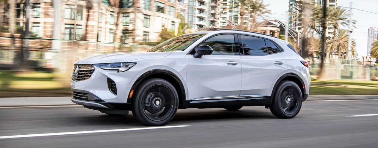 A white 2022 Buick Envision is shown driving through a city.