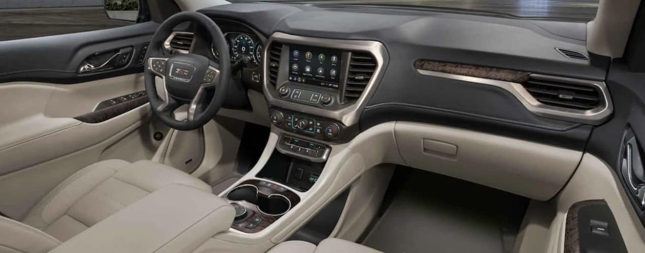 The interior of a 2022 GMC Acadia shows the steering wheel and infotainment screen.