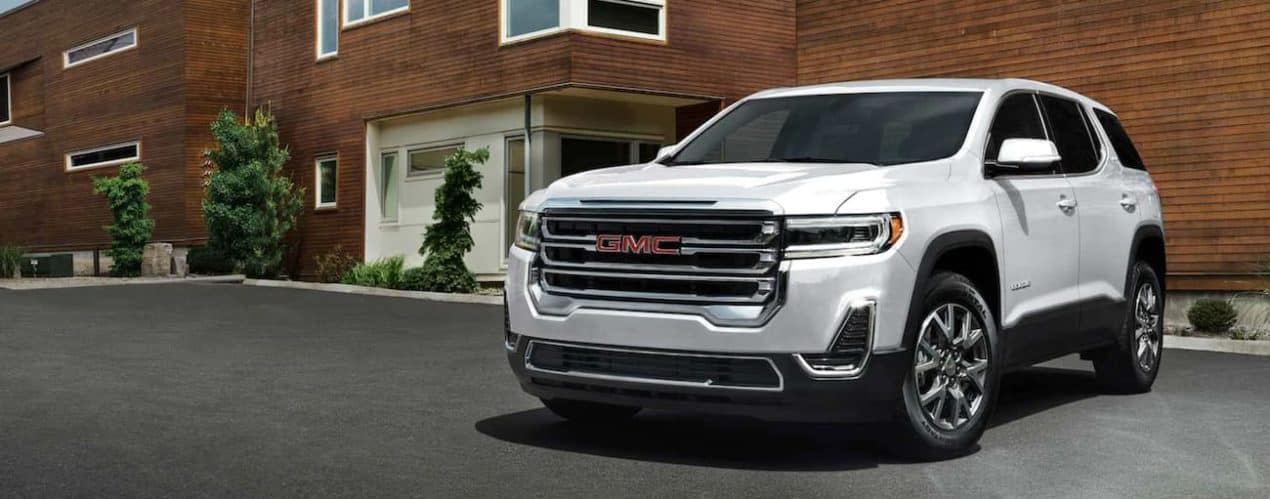 A white 2022 GMC Acadia is shown parked in front of a modern house.