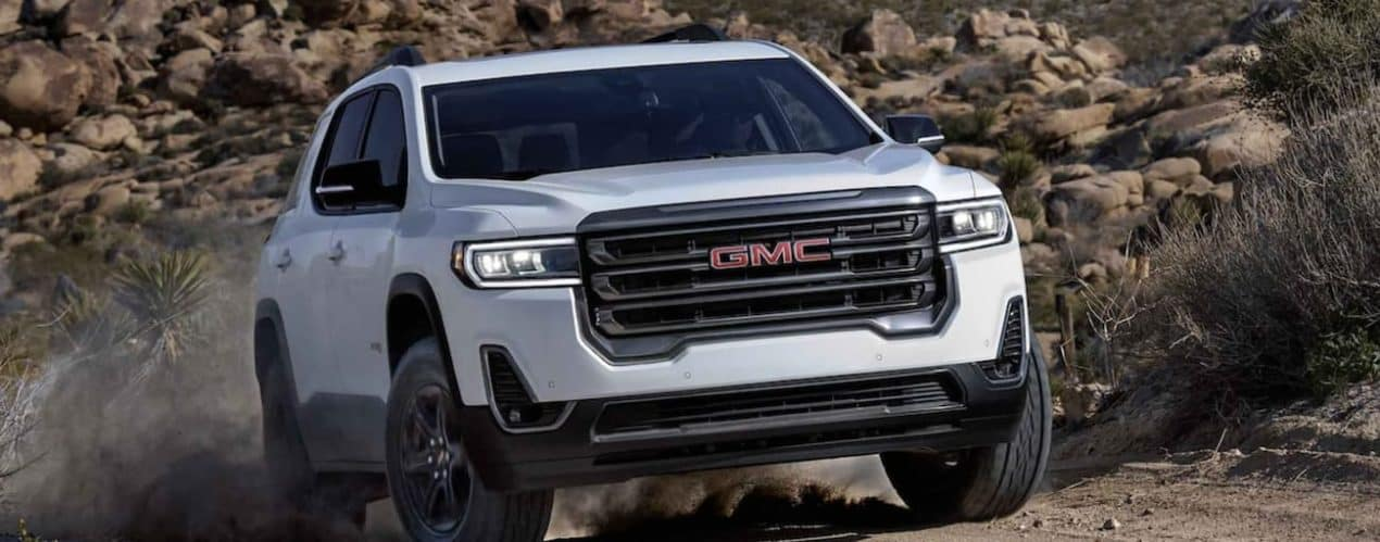 A white 2022 GMC Acadia is shown off-roading in the mountains.