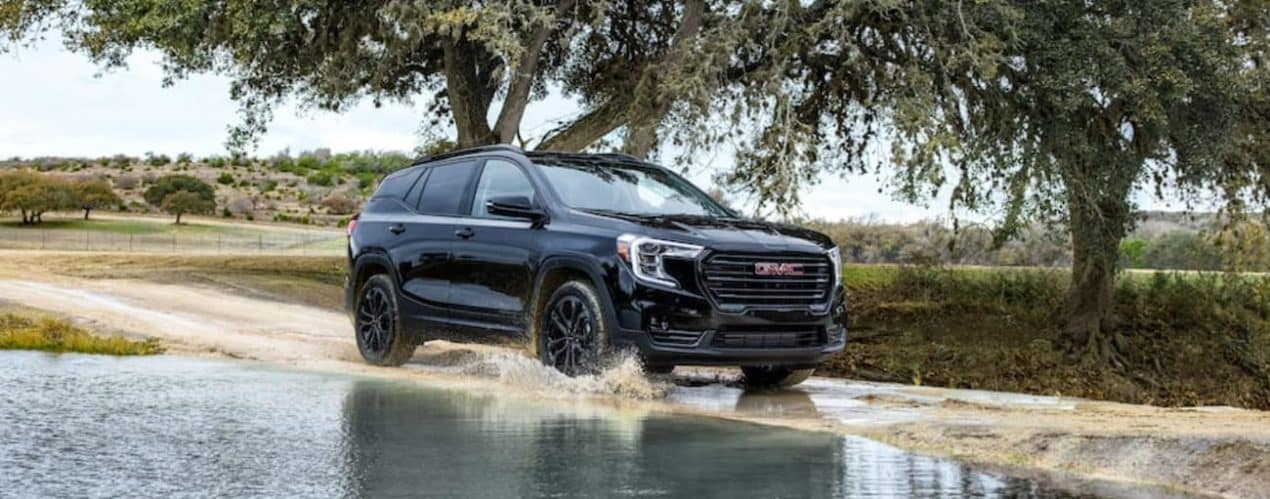 A black 2022 GMC Terrain is shown off-roading next to a puddle.