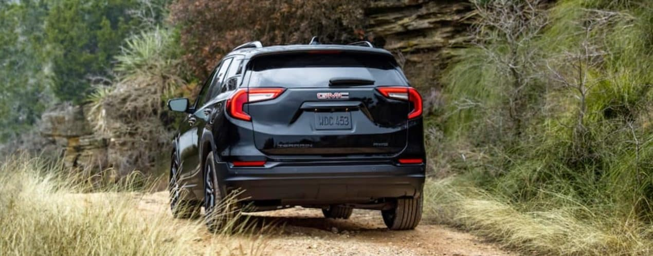 A black 2022 GMC Terrain is shown from the rear driving on a dirt path.