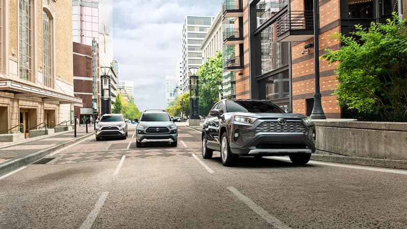 Three RAV4 SUVs in a staggered formation driving on a street