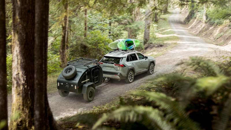 Toyota pulling a trailer through the forest
