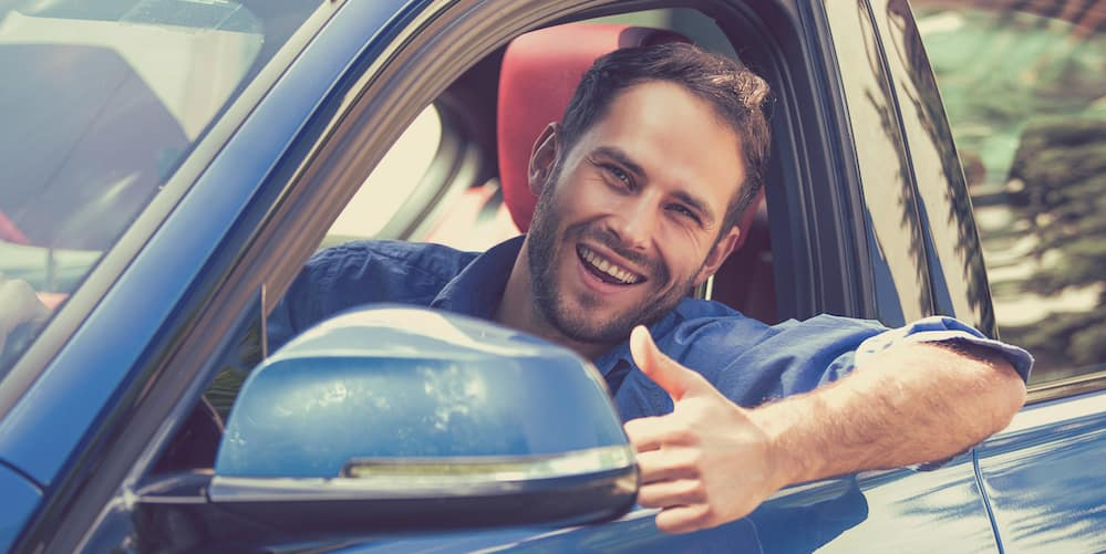 Man in a Used Car Giving Thumbs Up