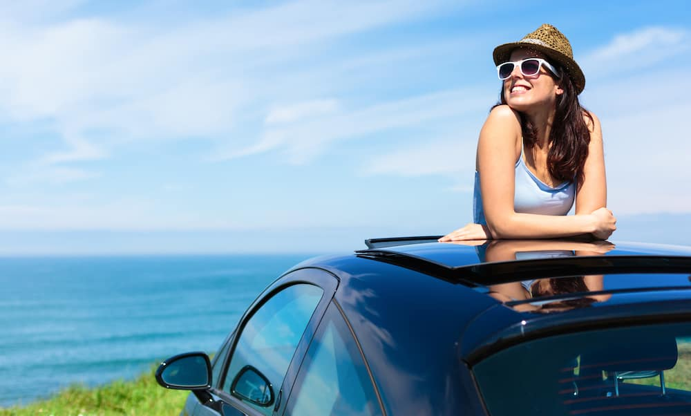 Woman Standing Up Out of Sunroof