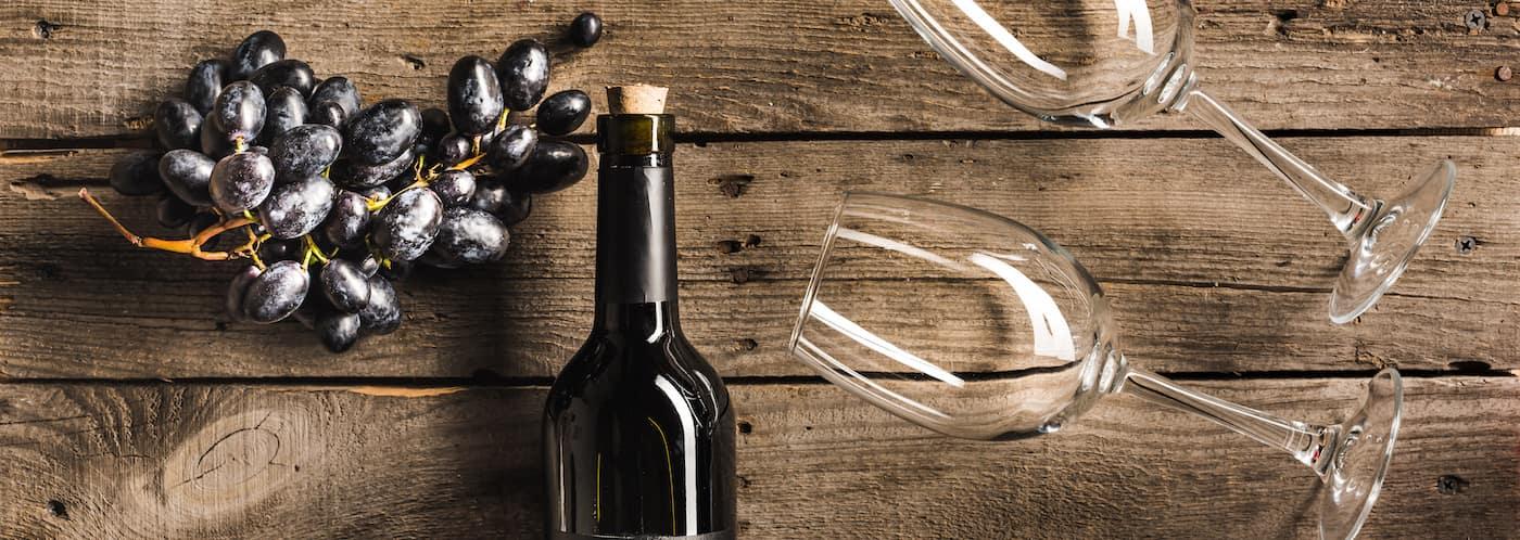 Wine Bottle, Glasses, Grapes on Table