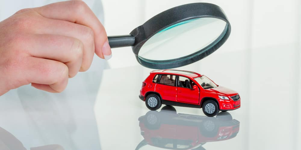 Examining Car with Magnifying Glass