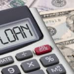 """Calculator with""""loan"""" written in screen sitting on top of money"""