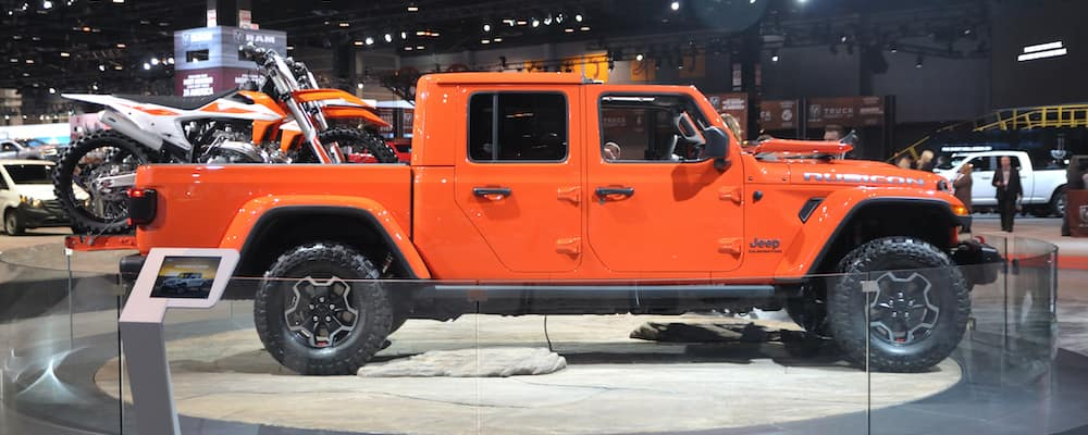 A bright orange Jeep Gladiator carrying an orange dirt bike in its truck bed.
