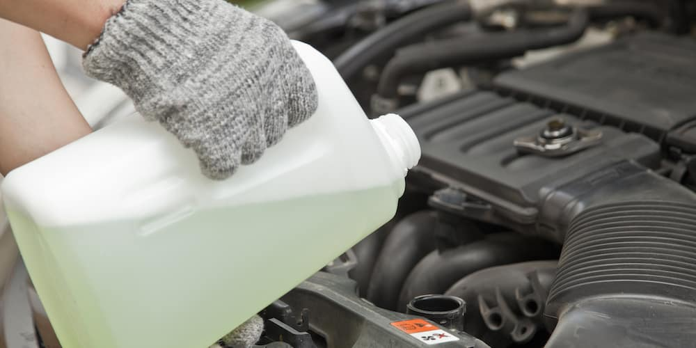 Jug of Green Coolant Being Poured into Car