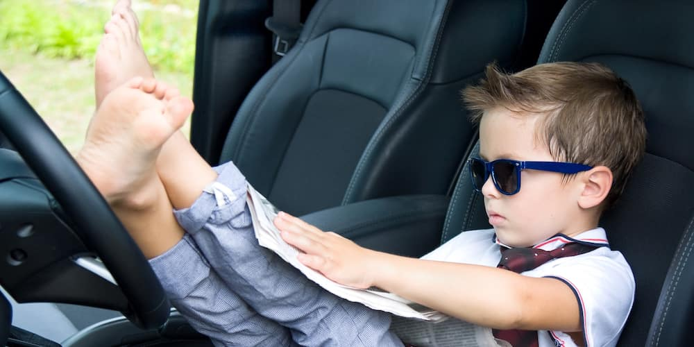 Young Boy Barefoot in Driver's Seat