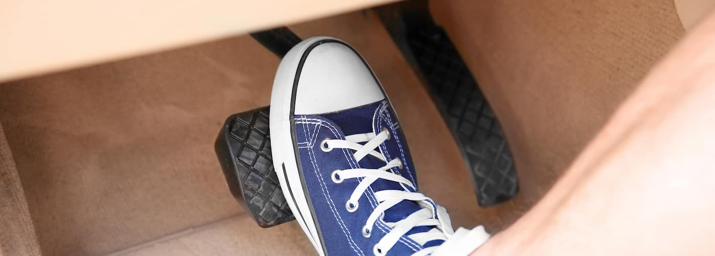 Foot in Blue Shoe Pressing on Brake Pedal