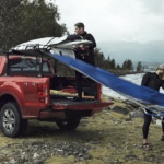 2020 Ford Ranger with open truck gate and bed and drivers unloading canoes