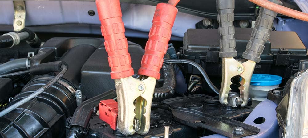Charging battery car with jumper cables with red and black clamps