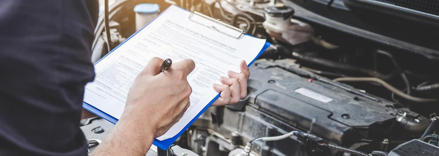 Mechanic Going Over a Checklist with Engine Open 236472016_xl-2015