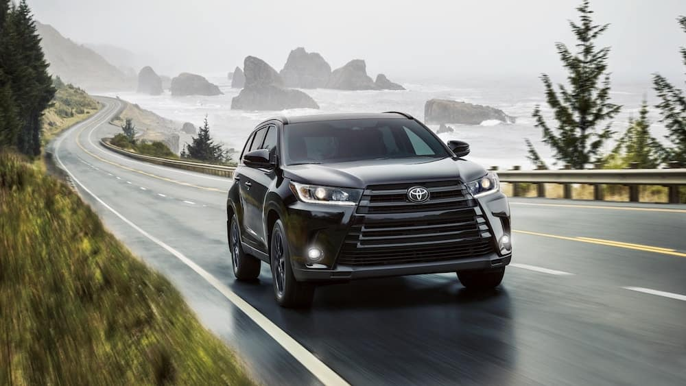Black 2019 Toyota Highlander driving down a road next to water