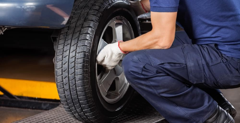 Service technician performing a tire rotation on a vehicle