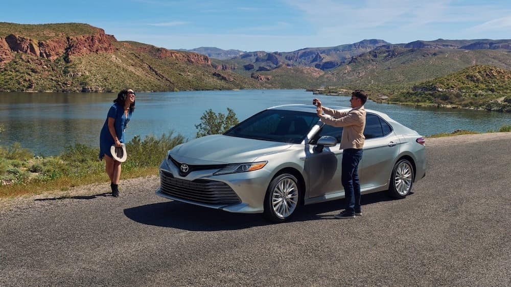 2020 Toyota Camry Hybrid Parked with Passengers Taking a Picture