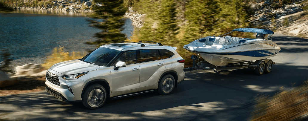 2020 Toyota Highlander towing a boat on lakeside road