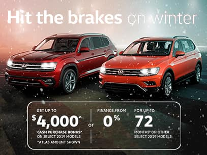 red atlas and orange tiguan with falling snow