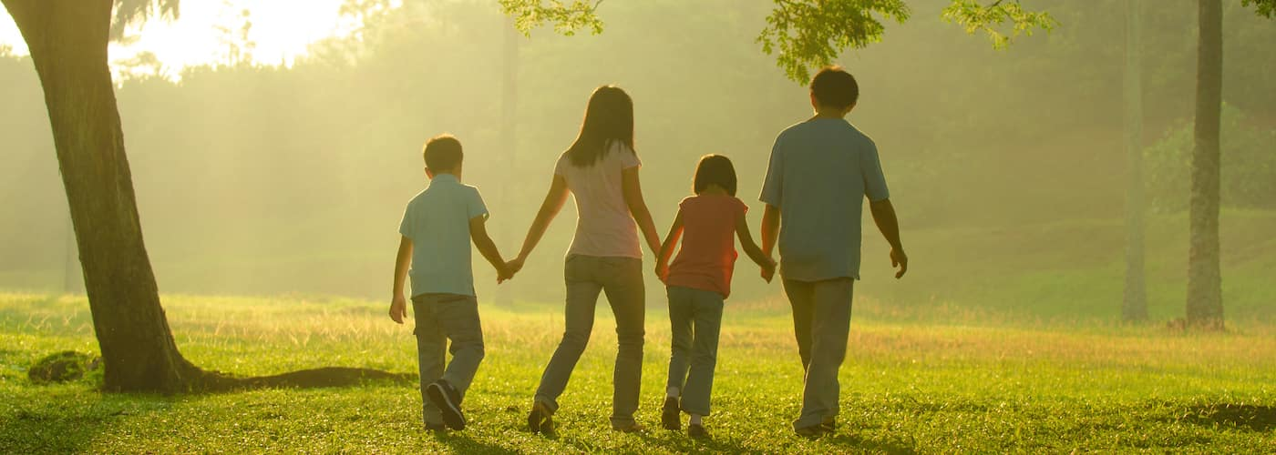 family walking together through park holding hands