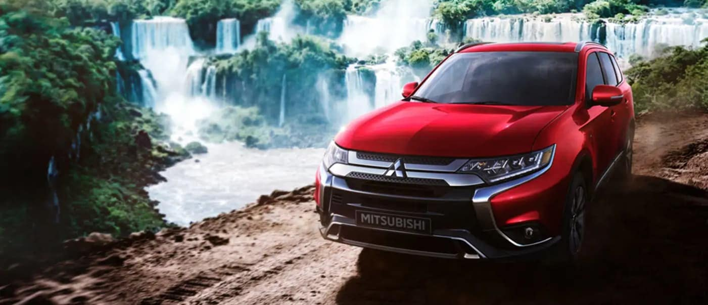 2020 Mitsubishi Outlander parked alongside waterfall