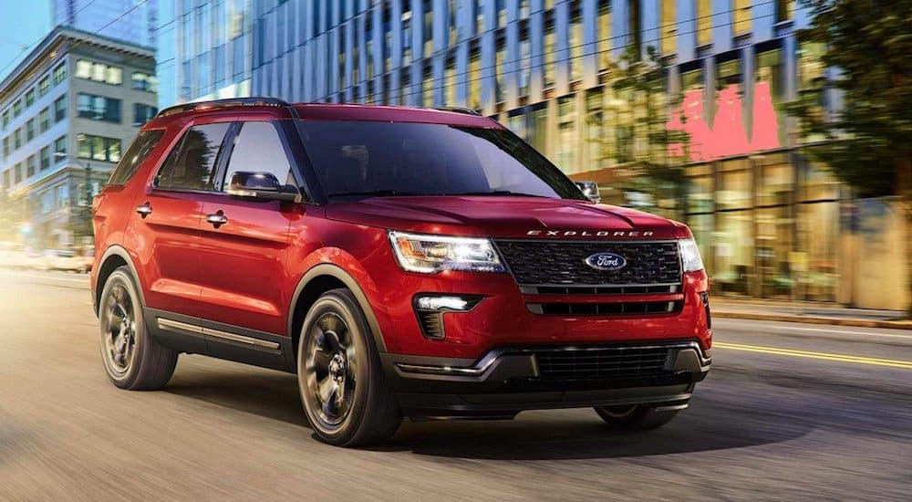 A red 2019 Ford Explorer races down a city street
