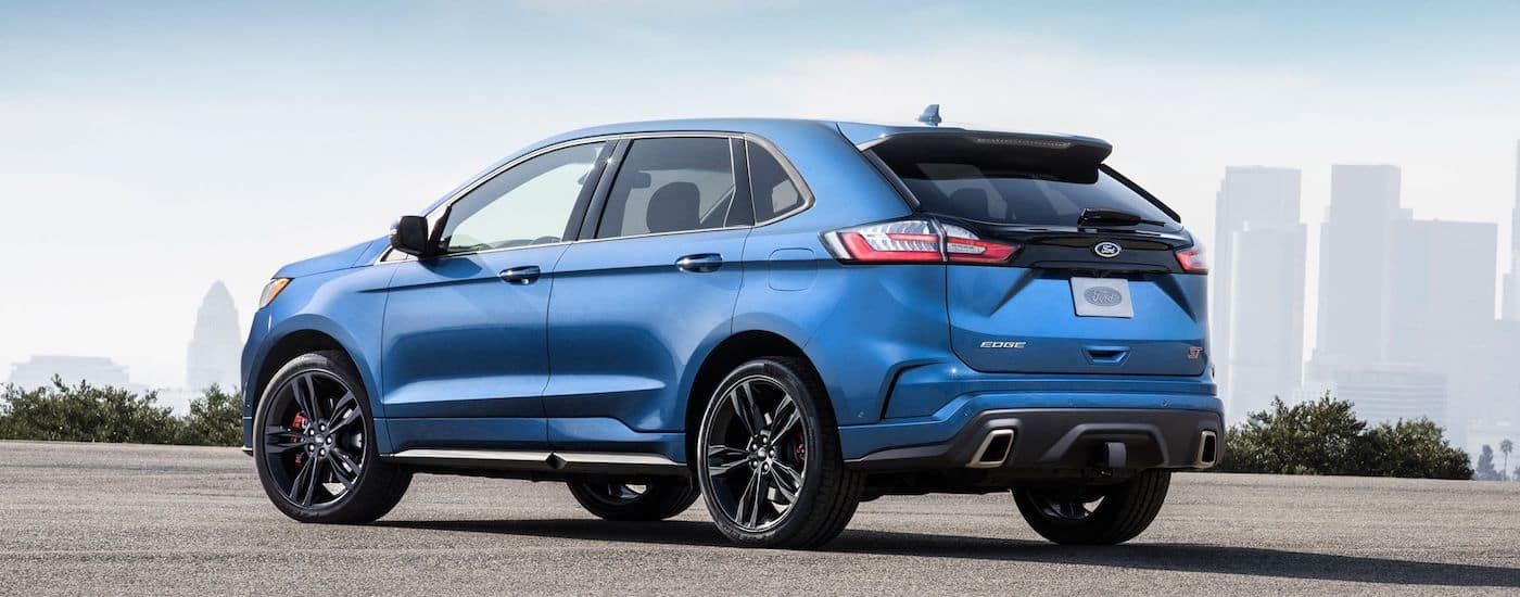 A blue 2019 Ford Edge sits parked with a city skyline in the background