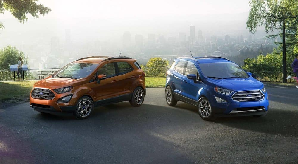 Orange and blue 2018 Ford Ecosport in park with city in background