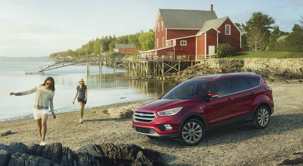 Women walking on beach with red 2018 Ford Escape and red building in background